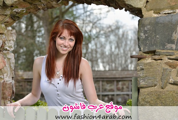 woman-with-red-hair-smiling-outside-at-a-fence-doorway