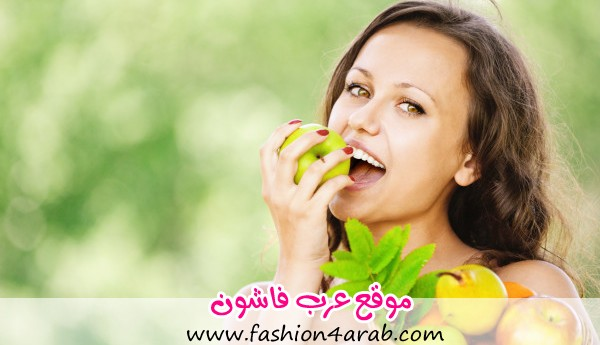 Portrait of young attractive brunette woman eating apple